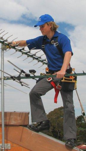 Сотрудник телевизионной службы устанавливает антенну на крыше.